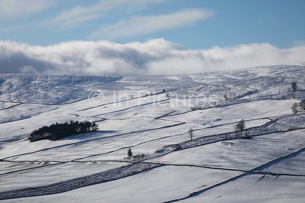 The farm hills in the Scottish Borders are covered in fresh snow on the 23rd of January 2021, Scotland, United Kingdom. The Borders is farmland the fields lie mostly empty during winter time.