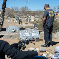 Members of the Muñoz family gather to place a headstone on the previously unmarked grave sites of Fernando and Dolores Muñoz at Hillcrest Cemetery in Gallup Saturday.