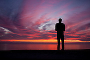 Man silhouetted against the sunset sky reflecting on the ocean in Southern California