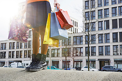 Low section view of woman holding shopping bags, Munich, Bavaria, Germany