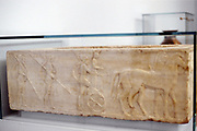 Ancient Greek warrior stepping into his chariot. Behind him are two hoplites carrying shields and spears. Hoplites formed the heavily armoured Greek infantry.  Bas-relief from limestone sarcophagus c.400 BC. Archaeological Museum of Thessaloniki