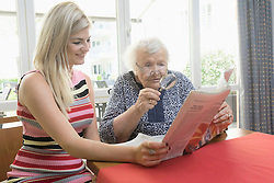 Woman reading newspaper with her mother at rest home, Eichenau, Bavaria, Germany