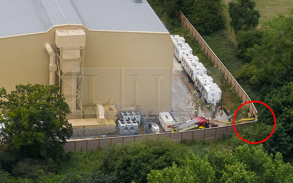 © Licensed to London News Pictures. 11/07/2019. Watford, UK. Fire engines can be seen at the back of Stage P at the Warner Bros film studios at Leavesden near Watford as they deal with the aftermath of a blaze that started overnight. Fire officers at to cut a large hole in the surrounding fence (R circled in red) to run their hoses in to the seat of the fire. The fire service were called in overnight after a fire started in one of the studios. The Harry Potter series was filmed here. Photo credit: Peter Macdiarmid/LNP