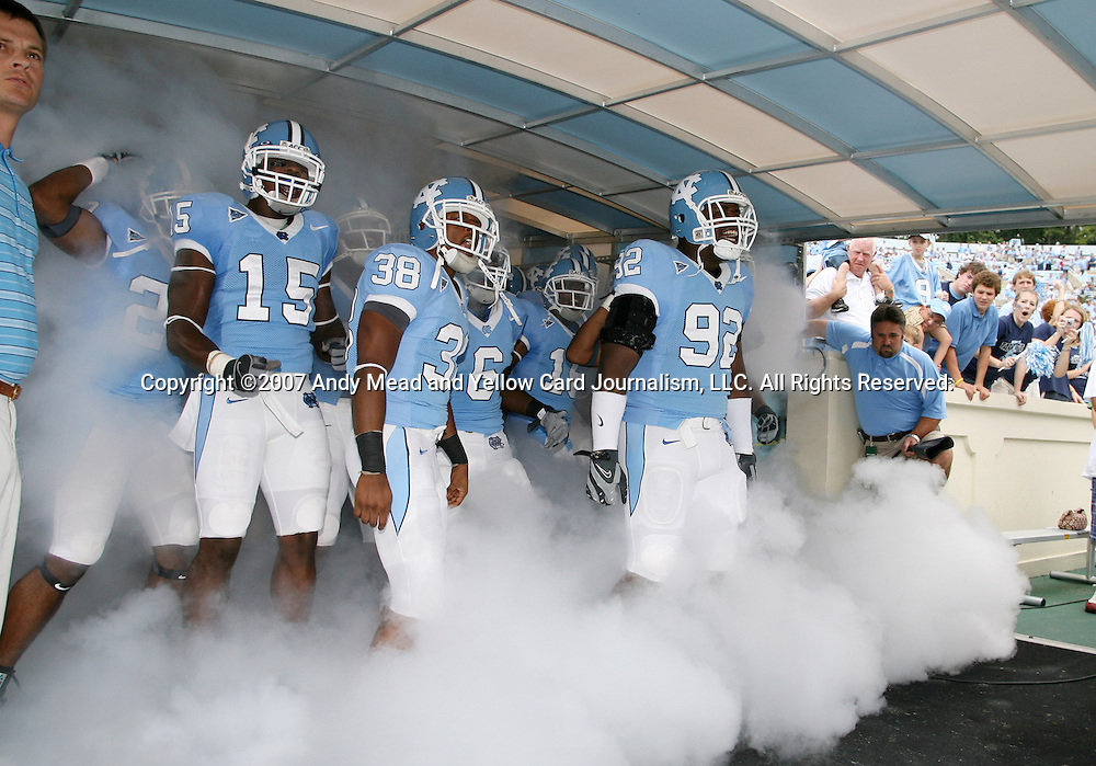 06 October 2007: UNC players, led by Anthony Parker-Boyd (15), Jermaine Strong (38), and E.J. Wilson (92) take the field. The University of North Carolina Tar Heels led the University of Miami Hurricanes 27-0 at halftime at Kenan Stadium in Chapel Hill, North Carolina in an Atlantic Coast Conference NCAA College Football Division I game.