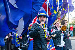 Top Hat wearing anti-Brexit and People's Vote campaigner Steve Bray and other members of his SODEM movement deliver a rowdy version of Fun Boy Three's The Lunatics Have Broken Out Of The Asylum on Great Peter Street, outside Four Millbank where all the major broadcasters have offices. The protest was designed to disrupt or intrude on any possible BBC lunchtime news broadcast from the roof of the building. Westminster, London, December 20 2018.