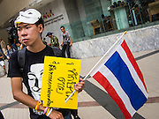 "14 JULY 2013 - BANGKOK, THAILAND:  A white mask protester on the plaza in front of the Bangkok Arts and Culture Centre. About 150 members of the so called ""White Mask"" movement marched through the central shopping district of Bangkok Sunday to call for the resignation of Yingluck Shinawatra, the Prime Minister of Thailand. The White Mask protesters are strong supporters of the Thai monarchy. They claim that Yingluck is acting as a puppet for her brother, former Prime Minister Thaksin Shinawatra, who was deposed by a military coup in 2006 and now lives in exile in Dubai.       PHOTO BY JACK KURTZ"