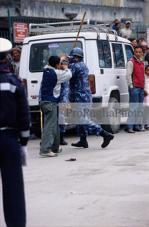 Kathmandu, 18 February 2005.  A policeman is blocking a young man from walking freely during the nation's Democracy Day. Authorities have, once again, cut off local telephone lines; public transport has also been banned for most of the day.
