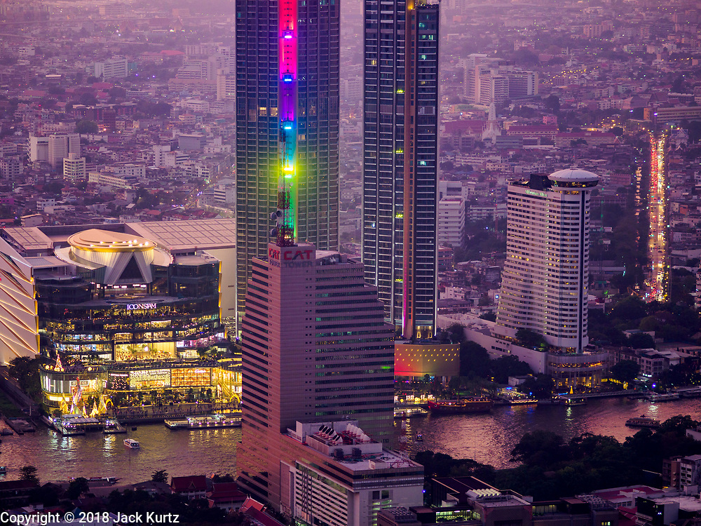 27 DECEMBER 2018 - BANGKOK, THAILAND:  IconSiam, Bangkok's newest high end shopping mall, seen at sunset from the rooftop observation deck of the King Power Maha Nakhon Tower. The MahaNakhon Skywalk, at the top of the King Power Maha Nakhon Tower, is 1,030 feet (314 meters) above street level. It is the tallest building and highest vantage point in Bangkok. The skywalk opened in November and has been drawing large crowds.     PHOTO BY JACK KURTZ