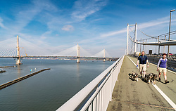 View of new Queensferry Crossing bridge under construction spanning River Forth and public walkway on Forth Road Bridge in Scotland, United Kingdom.