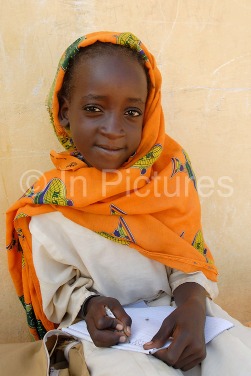 Young girl writes in her exercise book at Kendrig camp for Internally Displaced People. Kubri school - 1st grade. El Geneina, West Darfur, Sudan.