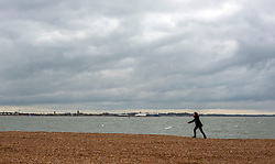 © Licensed to London News Pictures. 06/04/2014. Felixstowe, UK. A woman faces into the wind as she walks along the beach.  People under cloudy and windy conditions on the shoreline at Felixstowe today 6th April 2014. Photo credit : Stephen Simpson/LNP