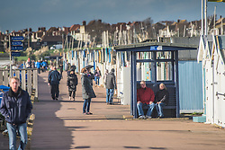 People enjoying a brisk walk along the seafront at Thorpe Bay in Southend on Sea, Essex, UK.