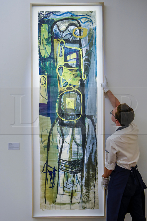 """© Licensed to London News Pictures. 17/07/2019. LONDON, UK. A technician presents """"Untitled Green"""", 1951-2, by Peter Lanyon at the preview of """"Brave New Visions: The Émigrés who transformed the British Art World"""", a new exhibition at Sotheby's gallery in New Bond Street which runs 17 July to 9 August 2019.  The show is also part of """"Insiders / Outsiders"""", a nationwide, year long festival celebrating refugees from Nazi Europe and their contribution to British culture.  Photo credit: Stephen Chung/LNP"""