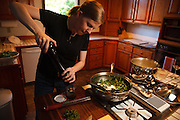 USA, Oregon, Eugene, young woman adding pepper to the balsamic vinnaigrette. MR