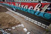Een auto rijdt langs de graffiti bij de Catherijnebak. De graffiti laat zien dat de weg weer onder water komt te staan. Waar nu de auto rijdt wordt weer onderdeel van Catherijnesingel.
