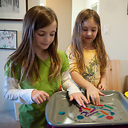 Two eight year old girls make paper at home using newspaper and colored scraps of paper.