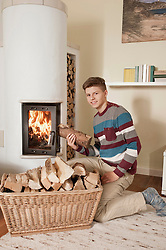 Teenage boy with log in front of fireside