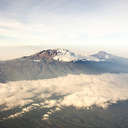 Mount Kilimanjaro Aerial View with Clouds. An aerial view of Mount Kilimanjaro, the highest peak in Africa, with a snow-covered peak.