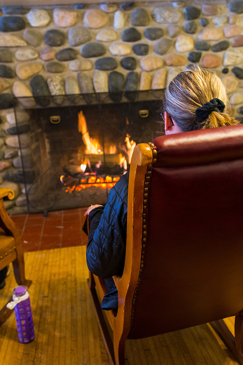 Participants in the Michigan DNR Becoming an Outdoors Woman program warm themselves by the fire in the main lodge at Bay Cliff Health Camp in Big Bay, Michigan.