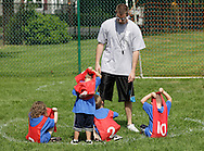 Middletown, New York - A coach watches children take off their numbered vests at the end of a youth soccer program at the Middletown YMCA on May 28, 2011.