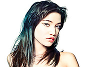 Asian woman with dark greenish/blue hair highlights, stares back into the camera, from the upper chest up to top of her head.
