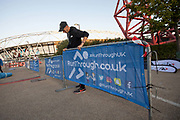 A steward sets up railings ahead of a 10 kilometre running event at the Queen Elizabeth Olympic Park in Stratford on the 21st September 2019 in East London in the United Kingdom. RunThrough is a London based running community who organise regular running events, training sessions as well as coaching.