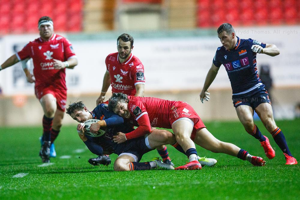 Llanelli, UK. 1 November, 2020.<br /> Scarlets winger Steff Evans tackles Edinburgh scrum half Henry Pyrgos the Scarlets v Edinburgh PRO14 Rugby Match.<br /> Credit: Gruffydd Thomas