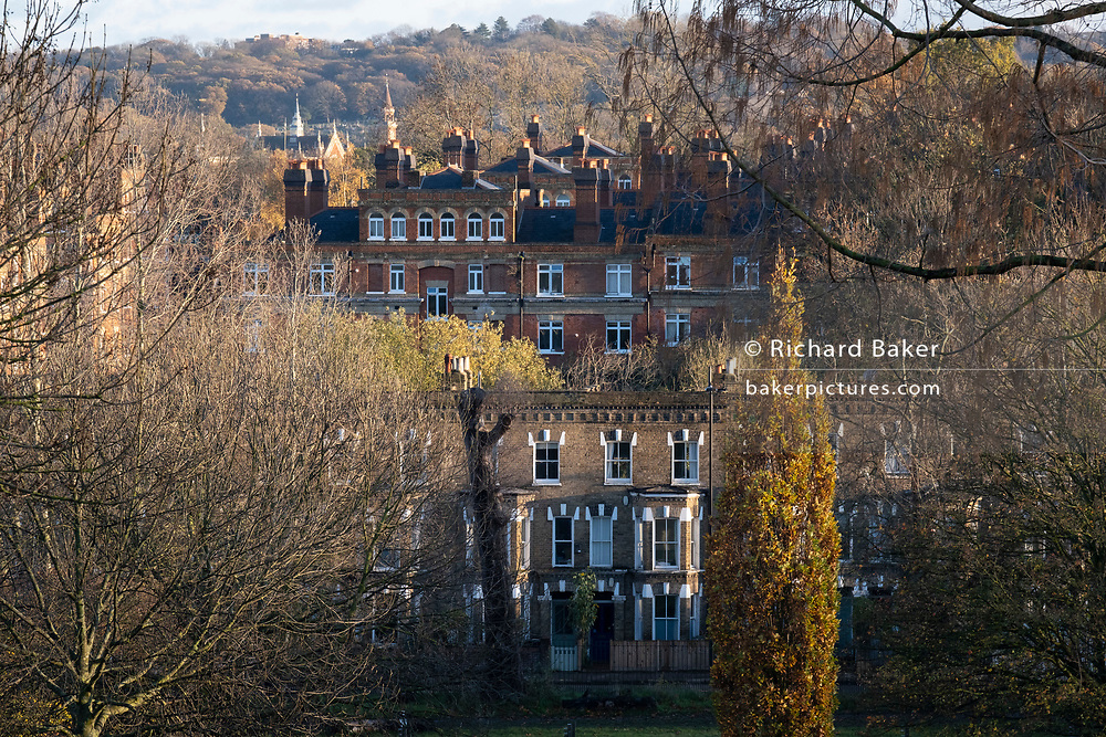 Suburban terraced houses and Victorian-era flats are seen from Herne Hill's Brockwell Park, on 19th November 2020, in Lambeth, London, England.