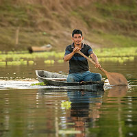 A smiling young man rows his canoe on the Yanayacu River in the headwaters of the Amazon River in Peru's Pacaya-Samiria National Reserve.