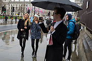 A man takes a photo with his phone with a Pret a Manger takeaway lunch hooked on his umbrella, in Parliament Square, Westminster, on 30th January 2020, in London, England.
