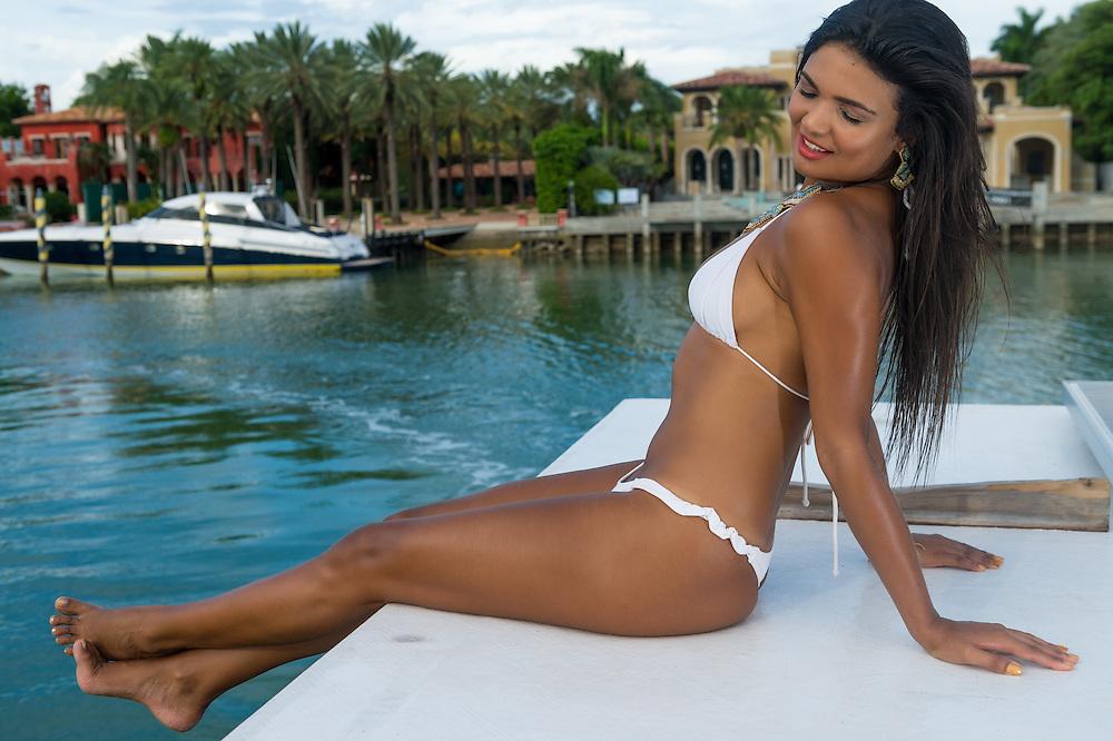 Sexy female wearing two piece bikini sitting on ta boat while navigating close to Miami Star Island