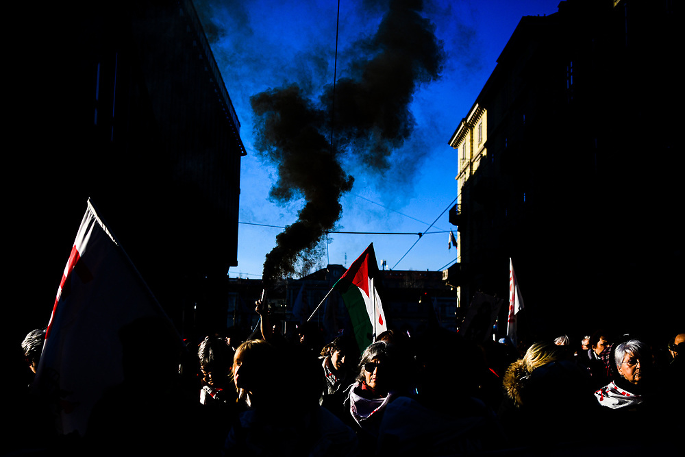 Turin, Italy - January 11, 2020: Silhouette of raised Palestinian flag waving against the sun at sunset during a demonstration.  Concept for conflict in the middle East, free palestine activism, justice for Palestinian