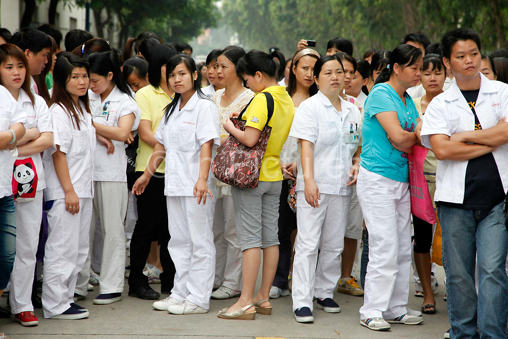 Workers on strike wait outside the Honda Lock factory in Zhongshan, China on Friday 12 June 2010. China's vast labor force is increasingly using strikes and walkouts as a way to demand higher salary and better compensation with success, many see this as the beginning of the end of China's role as the sweatshop of the world.
