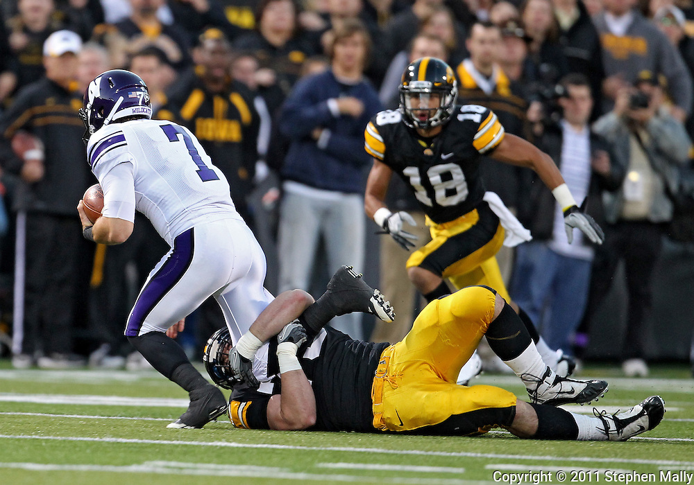 October 15, 2011: Northwestern Wildcats quarterback Dan Persa (7) is pulled down by Iowa Hawkeyes defensive lineman Dominic Alvis (79) during the first half of the NCAA football game between the Northwestern Wildcats and the Iowa Hawkeyes at Kinnick Stadium in Iowa City, Iowa on Saturday, October 15, 2011. Iowa defeated Northwestern 41-31.