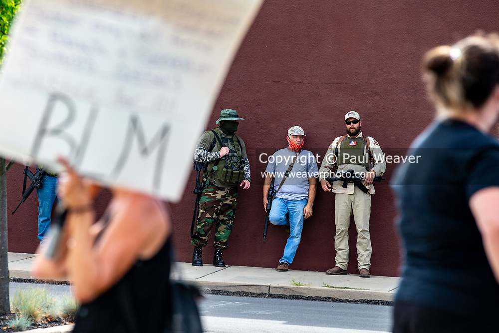 """Armed counter-protesters watch a Black Lives Matter protest from across a parking lot. About 200 people participated in a Black Lives Matter protest at Williamsport City Hall which was co-sponsored by Lycoming Tri-County NAACP and """"If Not Us, Then Who?"""""""