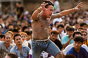 """15 MARCH 2014 - NAKHON CHAI SI, NAKHON PATHOM, THAILAND: A man in a trance rushes the stage at the Wat Bang Phra tattoo festival. Wat Bang Phra is the best known """"Sak Yant"""" tattoo temple in Thailand. It's located in Nakhon Pathom province, about 40 miles from Bangkok. The tattoos are given with hollow stainless steel needles and are thought to possess magical powers of protection. The tattoos, which are given by Buddhist monks, are popular with soldiers, policeman and gangsters, people who generally live in harm's way. The tattoo must be activated to remain powerful and the annual Wai Khru Ceremony (tattoo festival) at the temple draws thousands of devotees who come to the temple to activate or renew the tattoos. People go into trance like states and then assume the personality of their tattoo, so people with tiger tattoos assume the personality of a tiger, people with monkey tattoos take on the personality of a monkey and so on. In recent years the tattoo festival has become popular with tourists who make the trip to Nakorn Pathom province to see a side of """"exotic"""" Thailand.   PHOTO BY JACK KURTZ"""