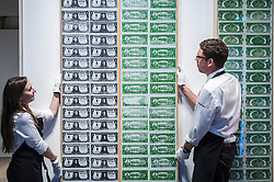 """© Licensed to London News Pictures. 08/06/2015. London, UK. Sotheby's technicians show """"One Dollar Bills"""" by Andy Warhol (est. £12m - £18m), at the preview of """"To the Bearer on Demand"""", a private collection of 21 works inspired by the US dollar, including Andy Warhol masterpieces, which will be auctioned on 1 and 2 July.  The collection is estimated to realise £50 million. Photo credit : Stephen Chung/LNP"""