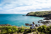 Woman sat on a bench on the north coast surrounded by views of the sea anmd the green headland and cliffs in Spring in Jersey, CI