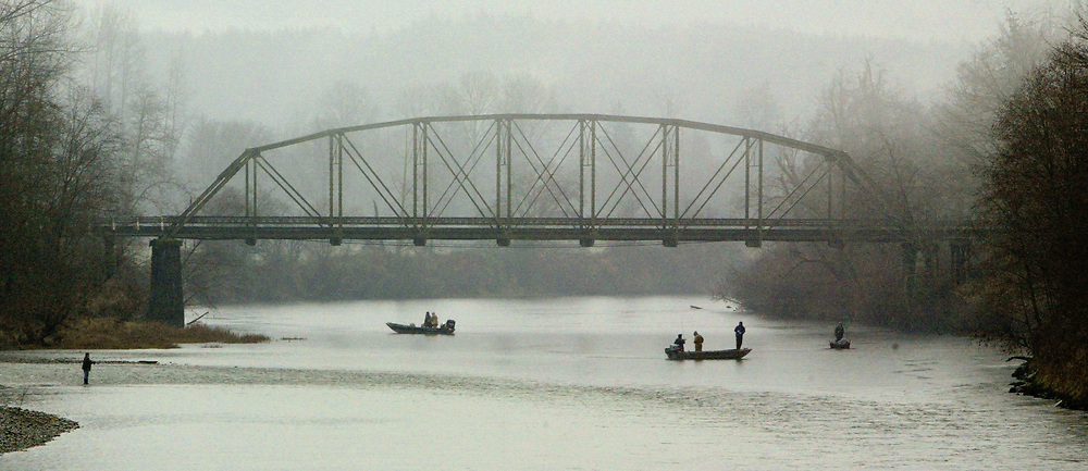Steelheaders drift along the Snoqualmie River waiting for a bite on a cold, wet, rainyafternoon in the Snoqualmie River under the Northeast Tolt Hill Road Bridge in Carnation. (Mike Siegel / The Seattle Times)