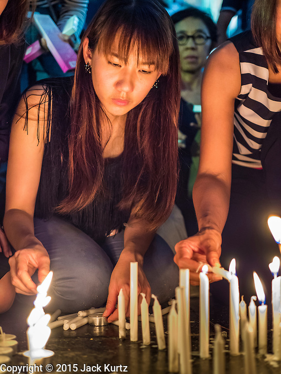 18 AUGUST 2015 - BANGKOK, THAILAND: A woman lights candles to honor the deceased at a makeshift memorial in front of Erawan Shrine, which was damaged by a bomb Monday night. An explosion at Erawan Shrine, a popular tourist attraction and important religious shrine in the heart of the Bangkok shopping district, killed at least 20 people and injured more than 120 others, including foreign tourists, during the Monday evening rush hour. Twelve of the dead were killed at the scene. Thai police said an Improvised Explosive Device (IED) was detonated at 18.55. Police said the bomb was made of more than six pounds of explosives stuffed in a pipe and wrapped with white cloth. Its destructive radius was estimated at 100 meters.      PHOTO BY JACK KURTZ