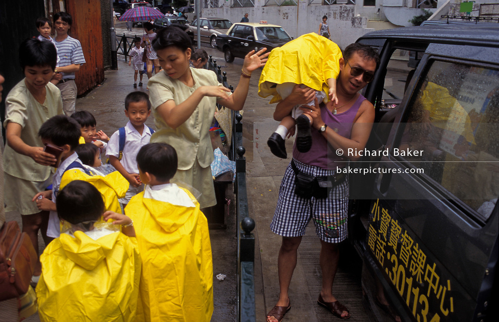 On a typical rainy day in south-east Asia, a nursery schoolchild is lifted over railings into local transport, on 10th August 1994, in Macau, China. Macau is now administered by China as a Special Economic Region (SER), home to a population of mainland 95% Chinese, primarily Cantonese, Fujianese as well as some Hakka, Shanghainese and overseas Chinese immigrants from Southeast Asia and elsewhere. The remainder are of Portuguese or mixed Chinese-Portuguese ancestry, the so-called Macanese, as well as several thousand Filipino and Thai nationals. The official languages are Portuguese and Chinese.