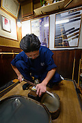 Fukutake Shinichi, sword polisher, polishing a sword, Setouchi city, Okayama Prefecture, Japan, February 2, 2014. The city of Bizen in central Japan is famous for Bizen-ware pottery. It is also one of Japan's main traditional sword making regions, home to Osafune sword-makers and polishers.