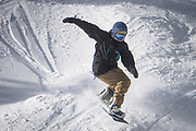 A snowboarder blows over a bump in fresh January powder at Monarch Mountain.