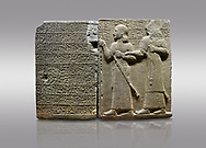 """Picture & image of Hittite monumental relief sculpted orthostat stone panel of Royal Buttress. Basalt, Karkamıs, (Kargamıs), Carchemish (Karkemish), 900-700 B.C. Anatolian Civilisations Museum, Ankara, Turkey.<br /> <br /> Hieroglyph panel (left) - Discourse of Yariris. Yariris presents his predecessor, the eldest son Kamanis, to his people. <br /> Right Panel - King Araras holds his son Kamanis from the wrist. King carries a sceptre in his hand and a sword at his waist while the prince leans on a stick and carries a sword on his shoulder. <br /> <br /> Hieroglyphs reads; """"This is Kamanis and his siblings.) held his hand and despite the fact that he is a child, I located him on the temple. This is Yariris' image"""".<br /> <br /> Against a gray background. .<br />  <br /> If you prefer to buy from our ALAMY STOCK LIBRARY page at https://www.alamy.com/portfolio/paul-williams-funkystock/hittite-art-antiquities.html  - Type  Karkamıs in LOWER SEARCH WITHIN GALLERY box. Refine search by adding background colour, place, museum etc.<br /> <br /> Visit our HITTITE PHOTO COLLECTIONS for more photos to download or buy as wall art prints https://funkystock.photoshelter.com/gallery-collection/The-Hittites-Art-Artefacts-Antiquities-Historic-Sites-Pictures-Images-of/C0000NUBSMhSc3Oo"""