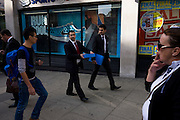 Two businessmen in dark formal suits carry identical blue boxes along a London street.