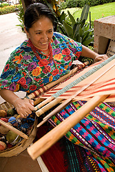 Central America, Guatemala, Antigua.  Woman weaving with traditional backstrap loom.  MR