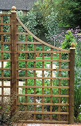 Square wooden trellis used as divider in a small garden