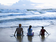 Tourists sit in the surf, Papanasham Beach (Beach of Redemption), Varkala, Kerala