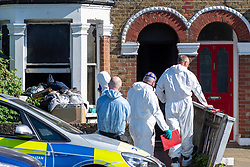 © Licensed to London News Pictures. 25/04/2020. London, UK. Forensic investigators wearing protective suits enter a property at the scene of a fatal house fire. A man has died in a house fire in Earlsfield, Wandsworth. Firefighters found the man in a ground floor bedroom. He was brought out of the property by fire crews but he died at the scene. London Fire Brigade was called at 07:36 BST and the fire was under control by 08:33 BST. Photo credit: Peter Manning/LNP