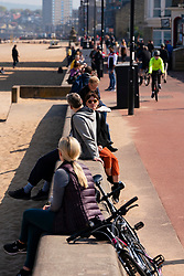 Portobello, Scotland, UK. 25 April 2020. Views of people outdoors on Saturday afternoon on the beach and promenade at Portobello, Edinburgh. Good weather has brought more people outdoors walking and cycling. Police are patrolling in vehicles but not stopping because most people seem to be observing social distancing. Promenade busy with people sitting on seawall.  Iain Masterton/Alamy Live News